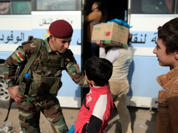 A Peshmerga soldier talks with a boy who is fleeing the fighting between Islamic State and the Iraqi army in Mosul, Iraq, November 14, 2016