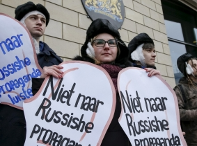 "Activists dressed as the artist Vincent van Gogh hold signs that say, ""Don't listen to Russian propaganda,"" outside the Dutch embassy in Kiev, Ukraine, February 5, 2016"