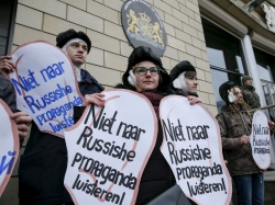 """Activists dressed as the artist Vincent van Gogh hold signs that say, """"Don't listen to Russian propaganda,"""" outside the Dutch embassy in Kiev, Ukraine, February 5, 2016"""