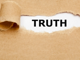 The word Truth appearing behind torn brown paper