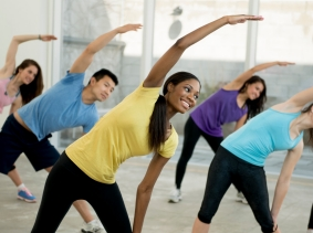 A group of young adults stretching in a dance class