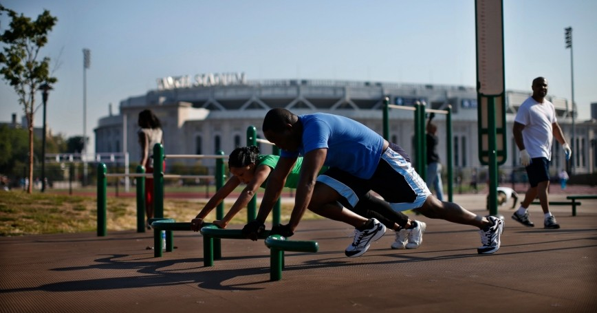 People work out at an outdoor exercise area at Macombs Dam Park in the Bronx, New York City, September 13, 2012