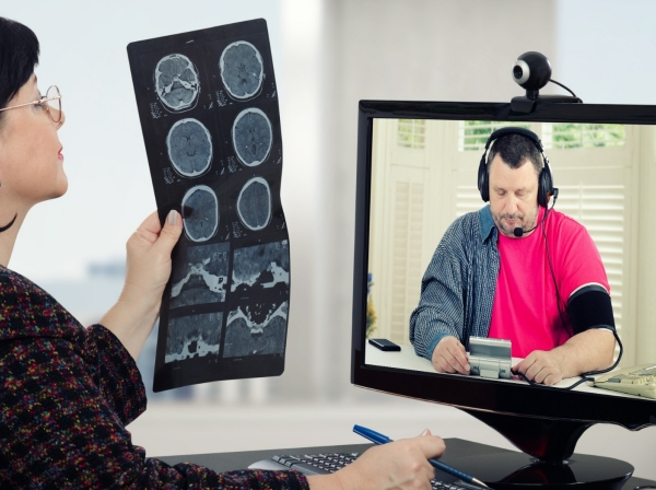 A doctor and a patient holding a telehealth session involving x-ray results and a blood pressure reading