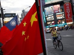 A woman rides a bike past Taiwan and China national flags during a rally held by a group of pro-China supporters calling for peaceful reunification, Taiwan May 14, 2016.