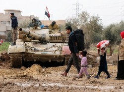 A family walks next to an Iraqi tank during a fight with ISIS militants in Rashidiya, north of Mosul, Iraq, January 30, 2017