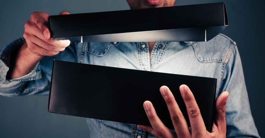 Man opening a black box with a light inside