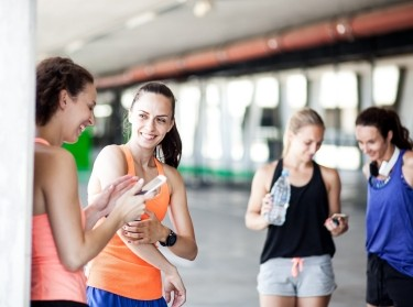 Group of women exercising and using their cell phones