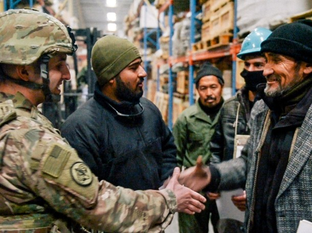 U.S. Air Force captain shakes hands with an Afghanistan National Army warehouse supervisor as they discuss storage and distribution for equipment and supplies in Kabul, Afghanistan, January 26, 2017
