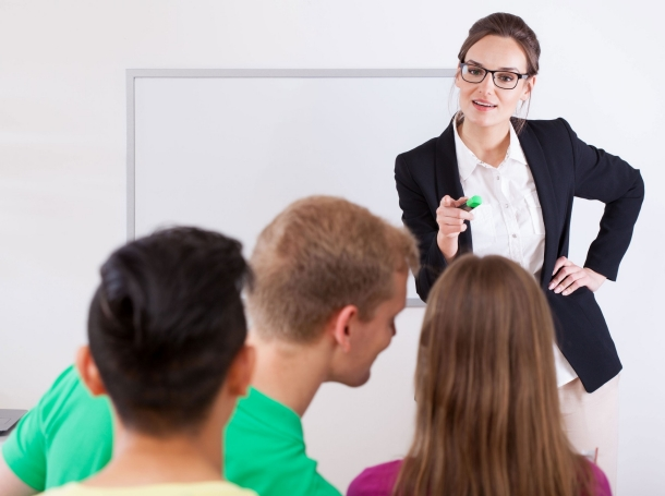 A teacher pointing to a student for talking in class