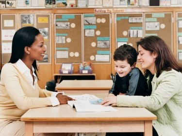A teacher meeting with a parent and her child in a classroom
