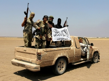 Fighters of the Syrian Islamist rebel group Jabhat Fateh al-Sham cheer on a pickup truck after a Russian helicopter was shot down in the north of Syria's rebel-held Idlib province, August 1, 2016