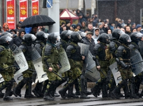 Law enforcement officers walk during a gathering denouncing the new tax on those not in full-time employment in Minsk, Belarus, March 25, 2017