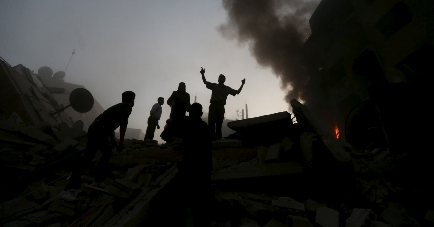 People rush to a site hit by what activists said was heavy shelling by forces loyal to Syria's President Bashar al-Assad in the Douma neighborhood of Damascus, June 16, 2015