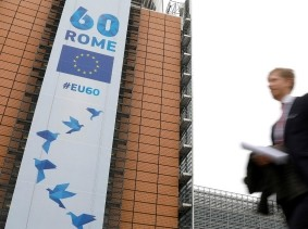 A man walks past the European Commission headquarters on which is displayed a banner celebrating 60 years after the signing of the Treaty of Rome, Brussels, Belgium, March 20, 2017