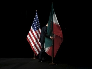 A staff member removes the Iranian flag from the stage after the Iran nuclear talks in Vienna, Austria, July 14, 2015