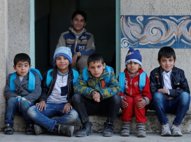Children pose after registering at a school and receiving new backpacks in Mosul, Iraq, January 23, 2017