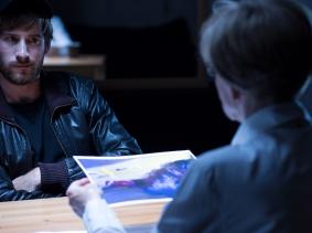 A man being interviewed by police in dark interrogation room