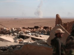 Smoke rises in the background as Syrian Democratic Forces fighters stand near rubble of a destroyed building, north of Raqqa, Syria, November 7, 2016