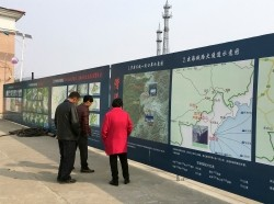 Locals read promotional boards about planned economic zones along the China-North Korea border in Nanping, China, March 27, 2017