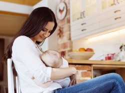 Mother breastfeeding at home