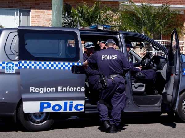 Police talk as they guard a house that was involved in pre-dawn raids in western Sydney September 18, 2014