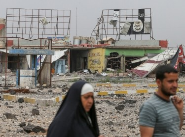 Displaced Iraqi people pass a torn Islamic State banner as the battle between the Iraqi Counter Terrorism Service and Islamic State militants continues nearby, in western Mosul, Iraq, April 23, 2017