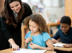 Teacher helping a third grade girl at her desk