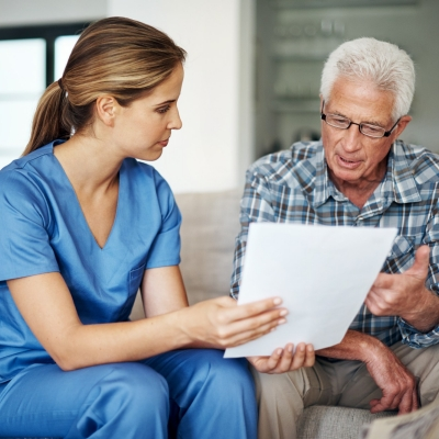 A nurse discussing paperwork with her senior patient