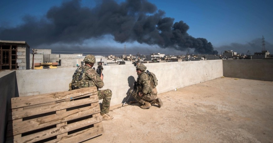 U.S. Army soldiers, deployed in support of Combined Joint Task Force - Operation Inherent Resolve, use a rooftop as an observation post in Mosul, Iraq, March 7, 2017