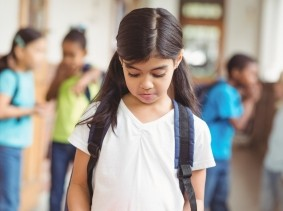 Girl being bullied by classmates in school corridor