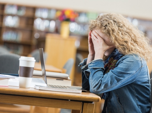 A stressed high school student studying in a library has a large coffee