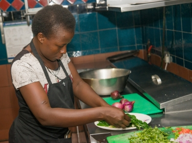 Kampala street food vendor Monica Kayagi makes a recipe during the Superfoods Cook-Off in December 2016