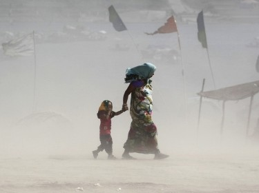A mother and her child walk along the Ganges river during a dust storm on a hot summer day in Allahabad, India, June 9, 2015
