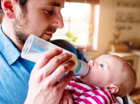 A father feeding his newborn baby