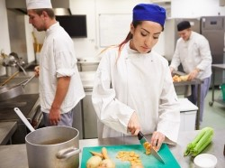 Woman chopping vegetables in a restaurant kitchen