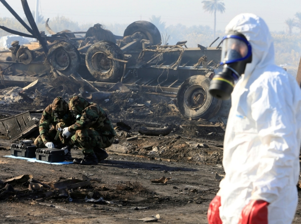 Chemical experts inspect the site of a suicide truck bomb attack at a petrol station in Hilla, Iraq, November 25, 2016