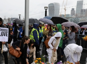 People lay flowers after a vigil to remember the victims of the attack on London Bridge and Borough Market, at Potters Field Park, London, June 5, 2017