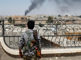 A Kurdish fighter from the People's Protection Units watches smoke rise after a coalition airstrike in Raqqa, Syria, June 16, 2017