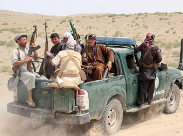 Afghan local police (ALP) sit at the back of a truck near a frontline during a battle with the Taliban at Qalay-i-zal district, in Kunduz province, Afghanistan August 1, 2015