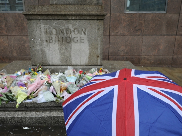 A pedestrian looks at floral tributes for the victims of the attack on London Bridge and Borough Market, June 6, 2017