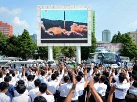 People watch a huge screen showing the test launch of intercontinental ballistic missile Hwasong-14 in this undated photo released by KCNA, July 5, 2017.