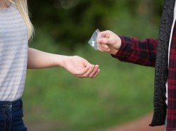 A teenage girl buying drugs from a boy outside school