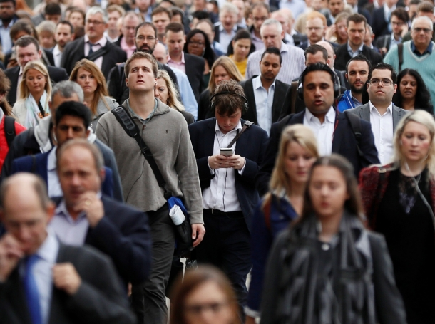 A commuter looks at his mobile phone as he crosses London Bridge during rush hour in London, Britain September 27, 2016