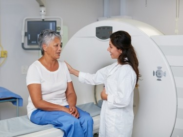 A woman on an MRI machine talking to her doctor