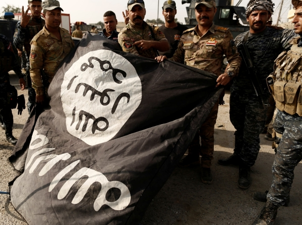 Iraqi soldiers pose with the Islamic State flag in al-Shura, Iraq, which they recaptured on October 30, 2016