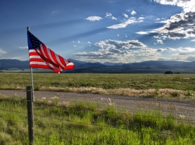 An American flag on a fence in the prairie