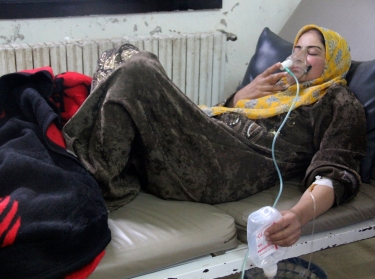 A woman affected by a gas attack breathes through an oxygen mask inside a field hospital in Kfar Zeita village, Hama, Syria, April 12, 2014
