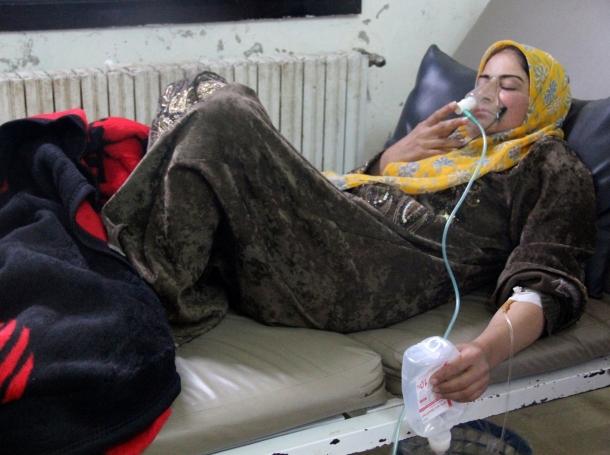 A woman affected by a gas attack breathes through an oxygen mask inside a field hospital in Kfar Zeita village, Hama, Syria, April 12, 2014
