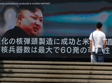 A passerby walks past a street monitor showing news of North Korea's fresh threat in Tokyo, Japan, August 9, 2017