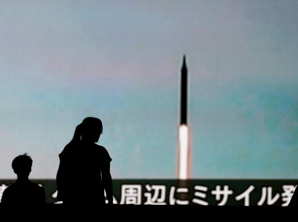 People walk in front of a monitor showing news of North Korea's fresh threat in Tokyo, Japan, August 10, 2017
